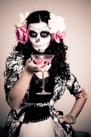 Una donna in costume Halloween in mano un bicchiere con liquido rosso Archivio Fotografico