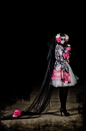 freak: A woman in Halloween costume and skull makeup holding flowers