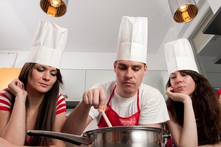 stirring: Three chefs stirring food in a pan