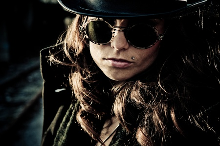 piercing: Face of mystery brunette woman wearing dark glasses and a hat, dark closeup outdoor portrait.