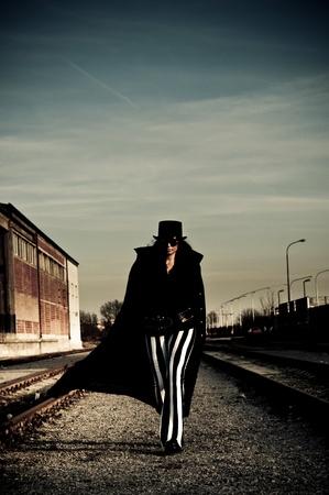 Spaventoso donna cercando in pantaloni a righe cammina accanto binari della ferrovia