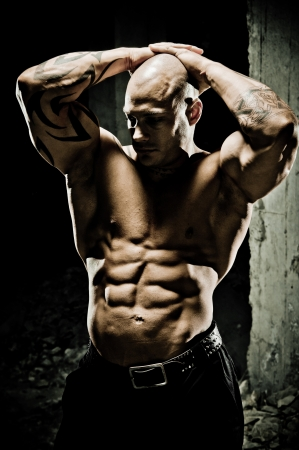 developed: Bodybuilder with his hands clasped above his head displaying his well developed abdominal muscles, overhead lighting highlighting musculature.