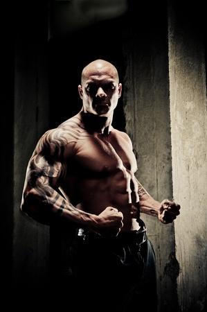 Handsome bodybuilder standing fit stringendo i pugni e flettendo i suoi muscoli delle braccia, illuminazione drammatica con riflessi sulla muscolatura.