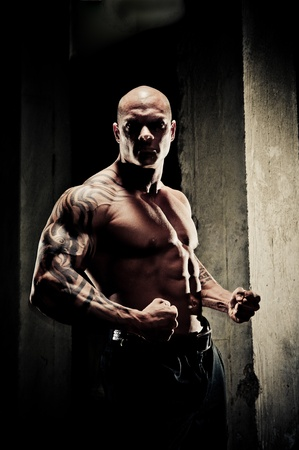 arm muscles: Handsome fit bodybuilder standing clenching his fists and flexing his arm muscles, dramatic lighting with highlights on musculature.