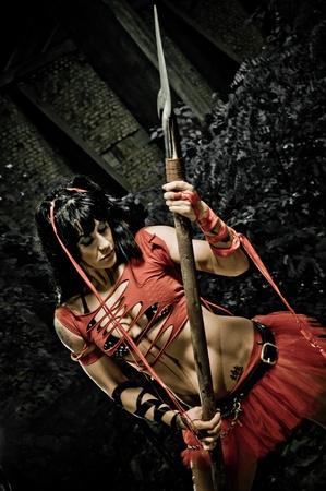 Bella donna in uniforme gladiatori in posa con una lancia mostra il suo corpo forte e in forma.