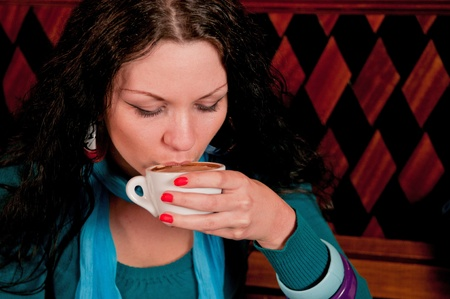 quench: Young woman with dark hair drinking coffee