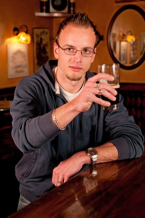 Man with a beer in bar giving a toast and smiling photo