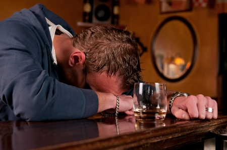 alcoholic drinks: Lonely drunk man who has had one too many glasses of alcohol at the bar and has passed out on the countertop