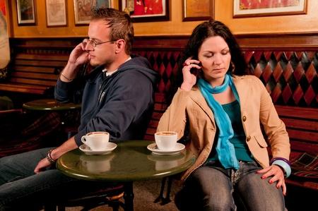 Coppia siiting a un tavolo davanti a un caff� dando l'un l'altro la spalla freddo a seguito di un disaccordo o alterco e seduto che guardano in direzioni opposte