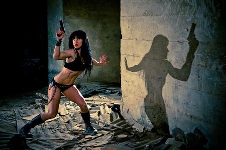 Sexy woman holding a gun wearing skimpy bikini looks furtively behind her in a dark alleyway  Stock Photo