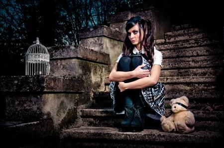 toy bear: Adolescent lolita schoolgirl sitting on stairs looking sad