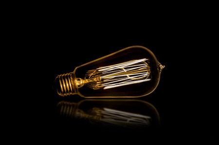 edison: Edison bulb on a reflective surface Stock Photo