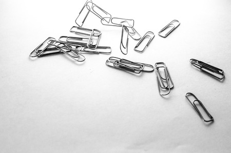 Paperclips scattered on a white background stationery metal office in a different order Stock Photo