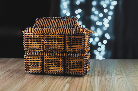 On the table is a house of matches, behind garlands, bokeh beautiful Christmas Stock Photo