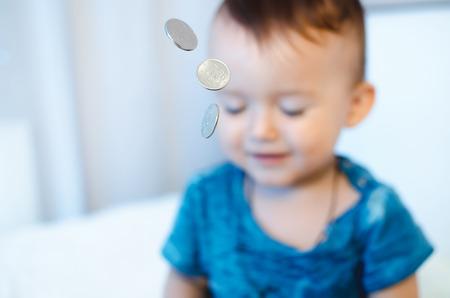 prestar atencion: El niño con las monedas en el primer plano con cerrada