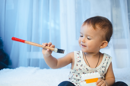 The child is sitting on the bed looking at the hammer holding it in his hands