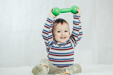 The child is involved in sports, fitness lifting dumbbell 版權商用圖片