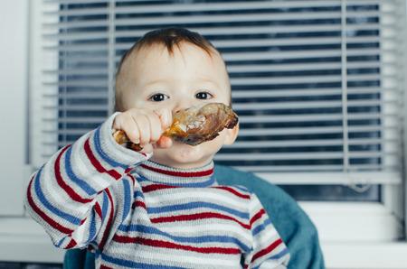 poquito: El niño que come con avidez de pollo, grasa y deliciosa en la cocina, muy hambriento Foto de archivo