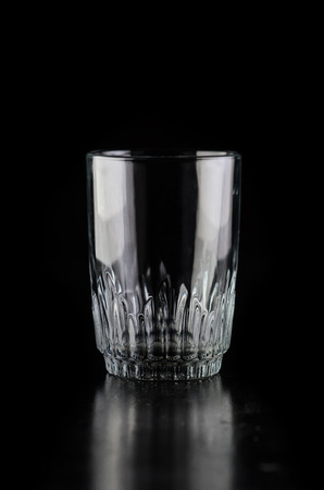 The glass horizontally on a black, old faceted Stock Photo