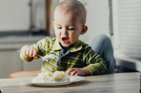 poquito: El niño come puré de patatas Foto de archivo