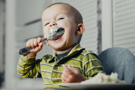 poquito: The child in the kitchen alone with a spoon eats mashed potatoes