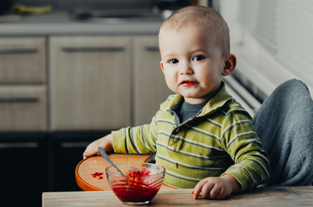eat smeared: the child in the kitchen eating jam red Stock Photo