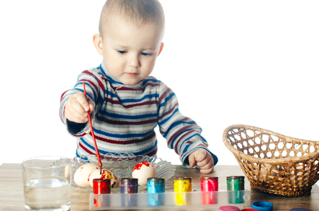 greengrass: The child paints Easter eggs with paints,on white background