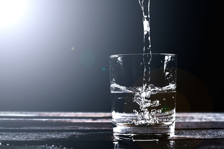 Water in a glass, isolated on a black background with splashes