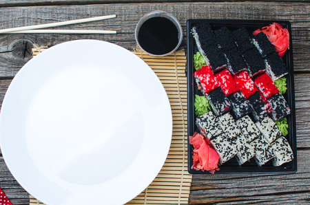 Sushi in a black container on a wooden table colorful and beautiful, white plate, blank