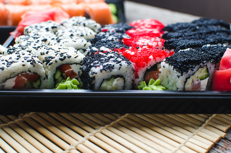 Sushi in a black container on a wooden table, delivery and order Stock Photo