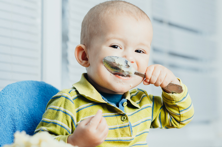 the child in the kitchen eating mashed potatoes and licks the spoon Stock Photo