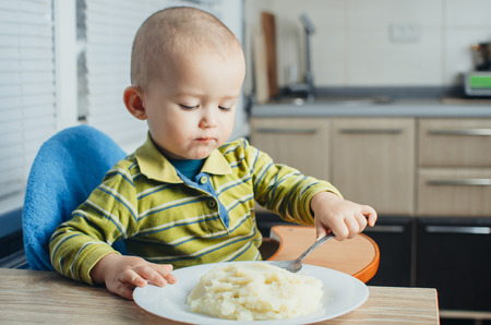 The child in the kitchen alone with a spoon eats mashed potatoes