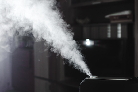 The steam from the humidifier at night in the dark black Фото со стока