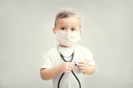 a small child on a gray background in the mask or cotton-gauze bandage with stethoscope in the hands