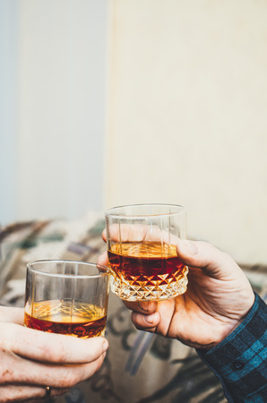 Hands with glasses of whisky, celebrate, relax and clink glasses