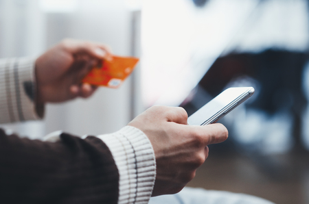 men hands, holding the phone and a visa card or another, entering data from the card