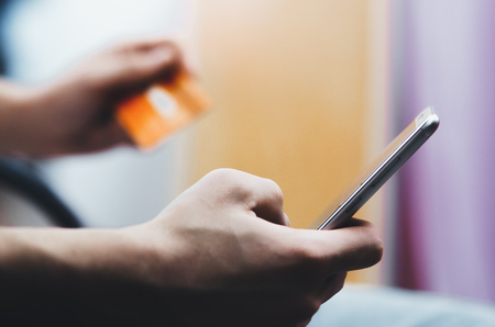 men hands, holding the phone and a credit card or another, entering data from the card Stock Photo