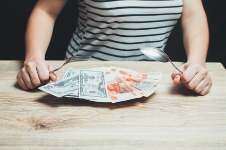 In the hand fork, on a plate money, metaphor, money for food