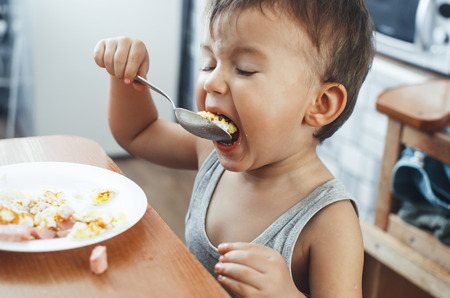 child t-shirt in the kitchen eating scrambled eggs, with a spoon