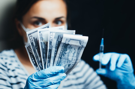 Money and syringe in the hands of the girl on a black background, paid medicine