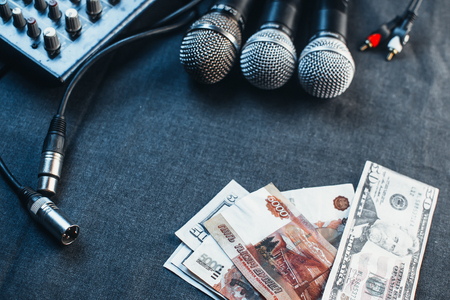 Music equipment, microphones, console and the money to pay the fee Stock Photo