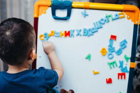 the little boy is studying the letters, using the easel with a magnetic surface Reklamní fotografie - 94273184