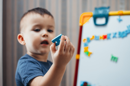 the little boy is studying the letters, using the easel with a magnetic surface