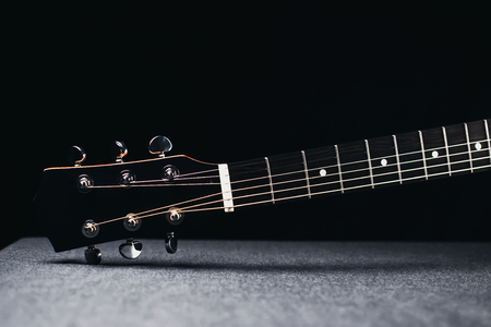 part of the guitar, neck and headstock on black background picture