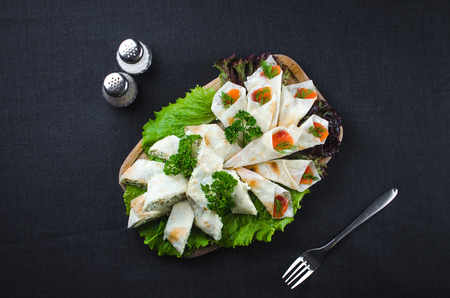 on the background of dark fabric pita roll with salmon and Philadelphia cheese, beautifully laid out, next fork and Solyanka, with salt and pepper