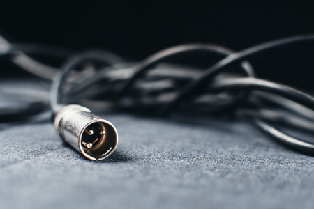 XLR, connector with wires on a dark fabric background in the Studio Stock Photo