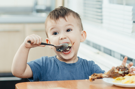 child in the kitchen eating mashed potatoes, spoon, next to the plate is a piece of chicken meat Stock Photo