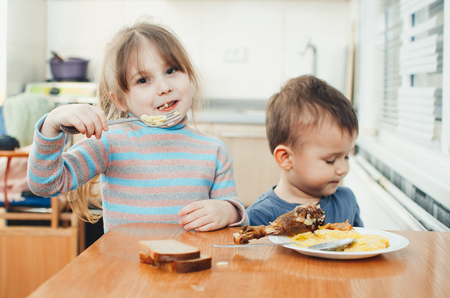 Children in the kitchen eat meat and mashed potatoes, very fun, share and feed each other Banco de Imagens