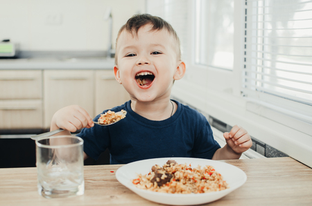 beautiful cute baby eats rice with a spoon in the kitchen, very fun Stock Photo
