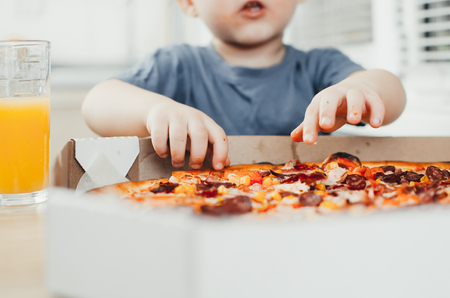 The child in the kitchen eats a huge pizza and drinks juice, a lot of fun